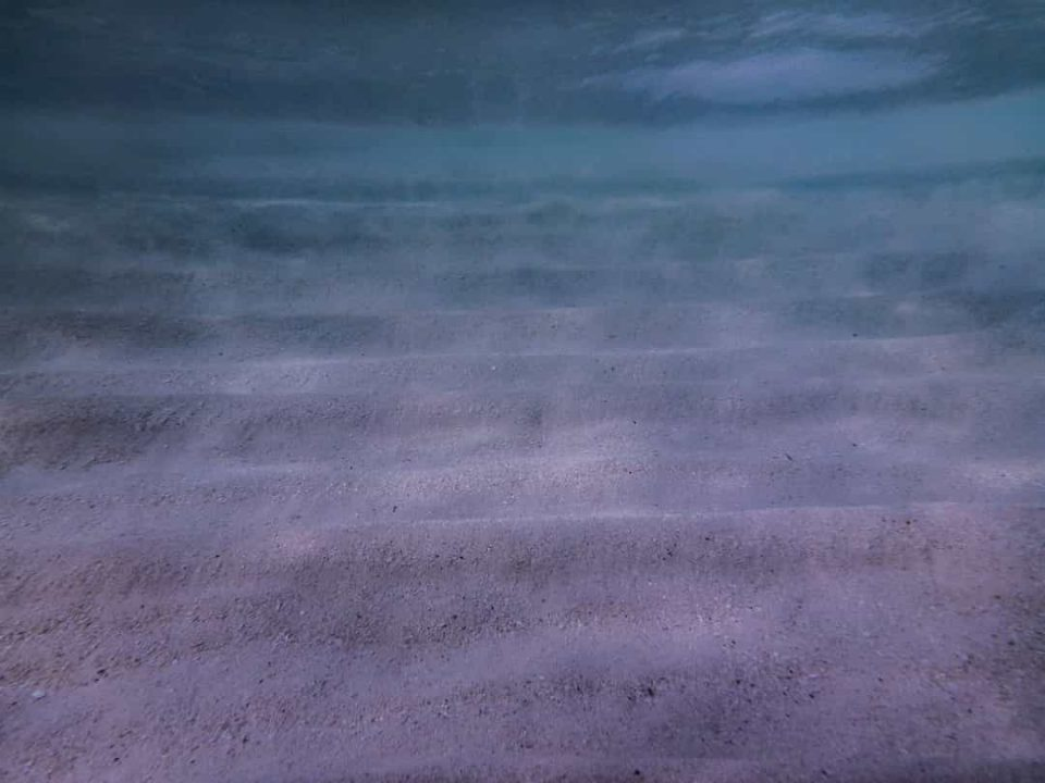 Underwater image of sand with darkening shades of blue as water deepens